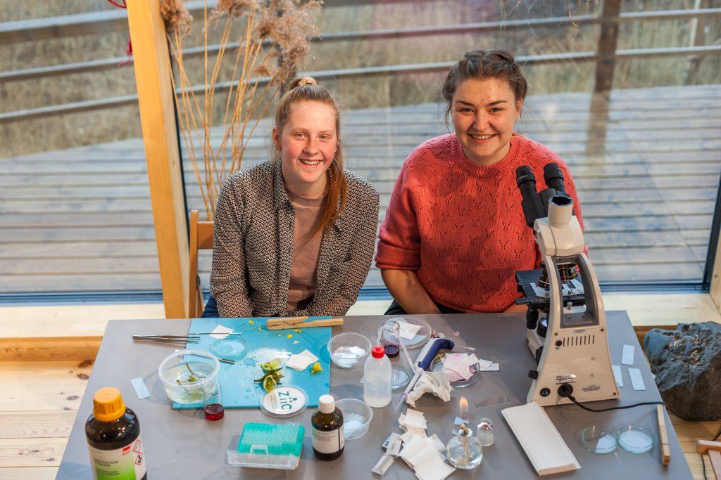 Divas meitenes sēž pie galda, uz kura stāv dažādi dažādi izpētes materiāli bioloģijā