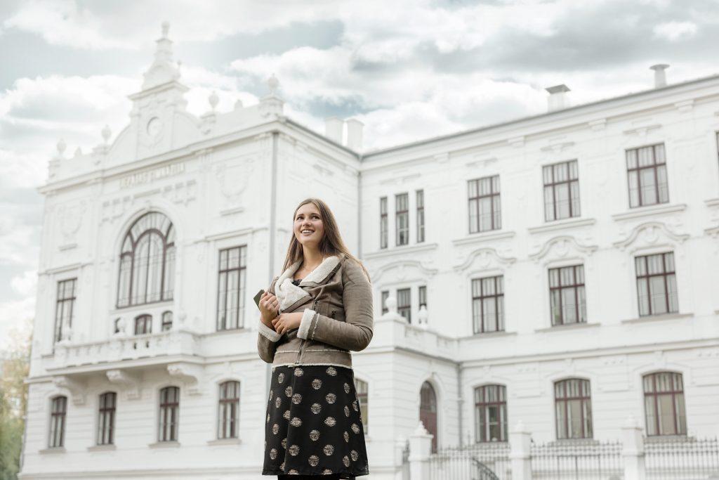 Meitene ar grāmatām rokās, fonā redzama liela, balta ēka