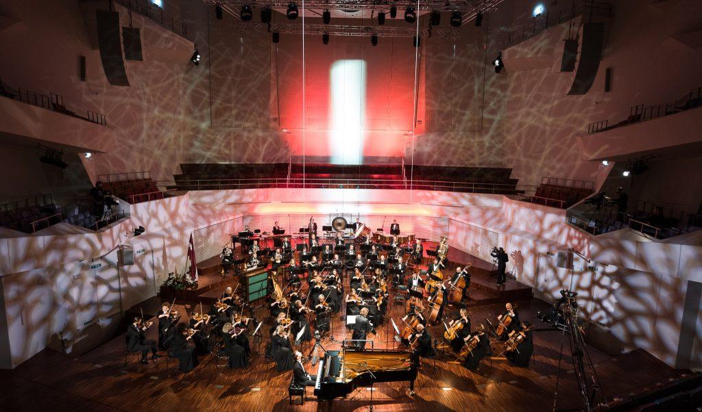 """koncertzālē """"Lielais dzintars"""" notiek svētku koncerts. Zāle izgaismota sarkanbaltsarkanās krāsās."""