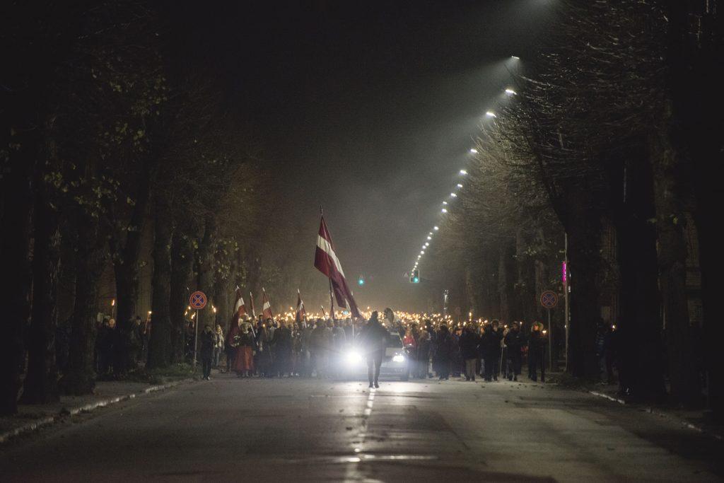 cilvēki ar gaismas lāpām un lielu, plīvojošu Latvijas karogu