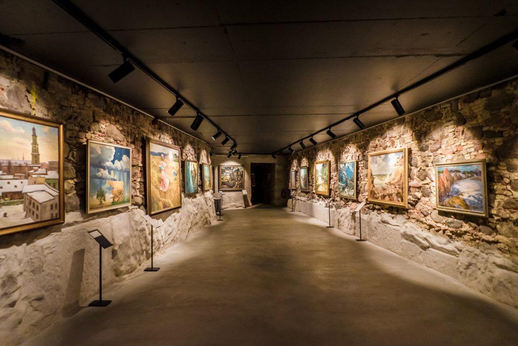 izstāžu galerija izgaismotā pagraba telpā ar gaišām sienām
