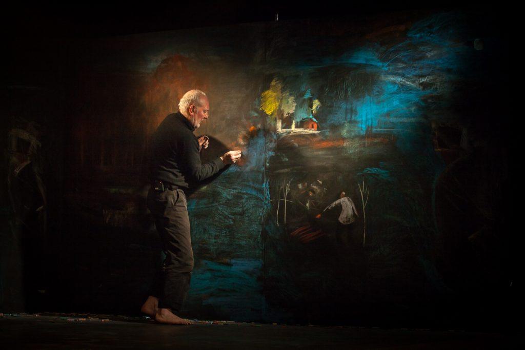 Sirms vīrietis tumšās drēbēs uz tumša fona, zīmē krāsainus zīmējumus uz tumšas sienas