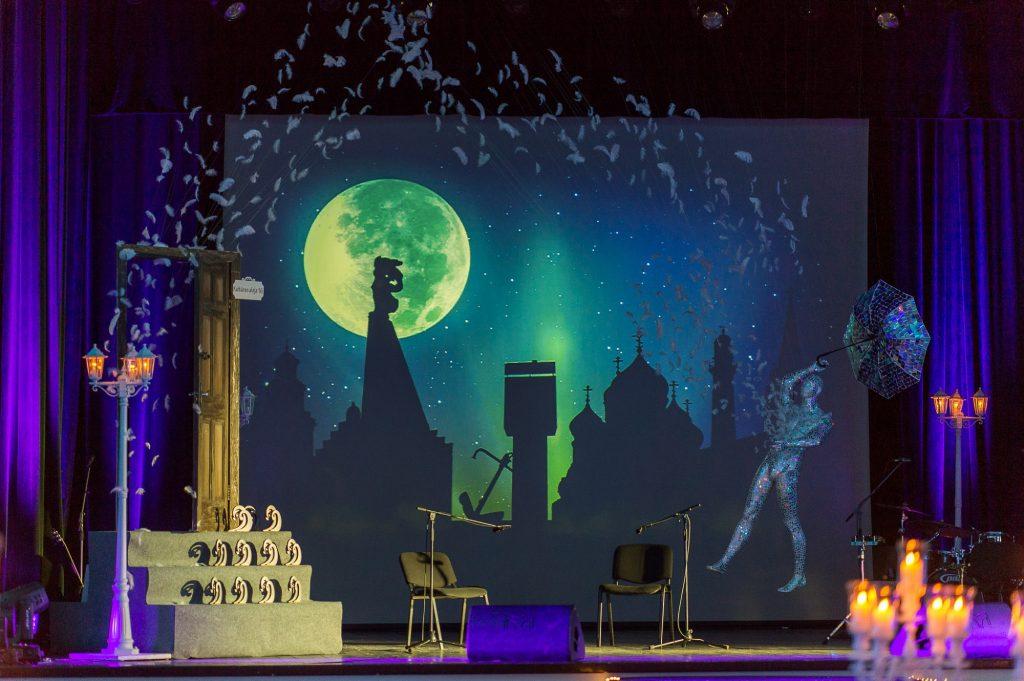 Skatuves noformējums tumši zilos un zaļos toņos ar video vizualizāciju un bagātīgu skatuves noformējumu