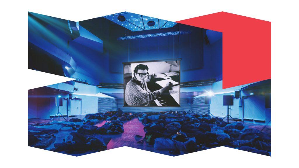 Pasākuma makets zilos toņos ar koncertzāli, izgaismotu video ekrānu centrā, kurā atainots melnbalts attēls, zālē guļošiem cilvēkiem uz zāles grīdas