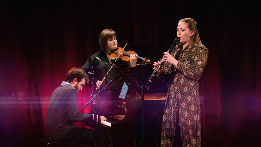 Trīs mūziķi uz skatuves sniedz koncertu
