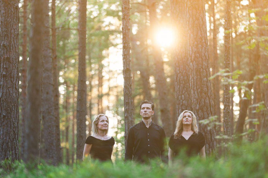 trīs cilvēki starp kokiem mežā un aiz viņiem caur kokiem spīd saule