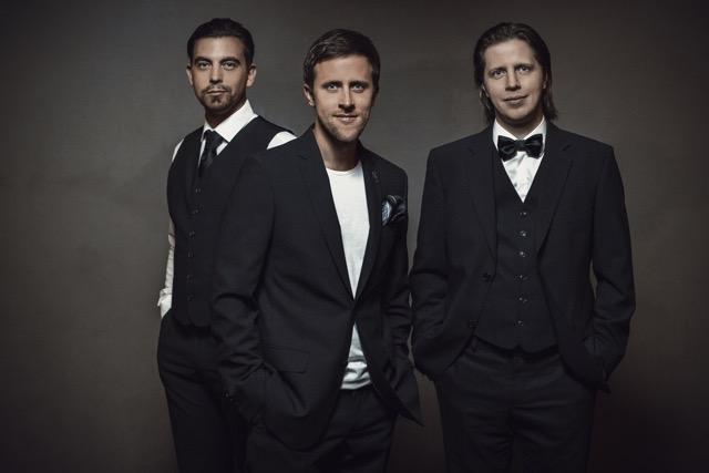 Trīs vīrieši tumšās drēbēs, uz tumša fona