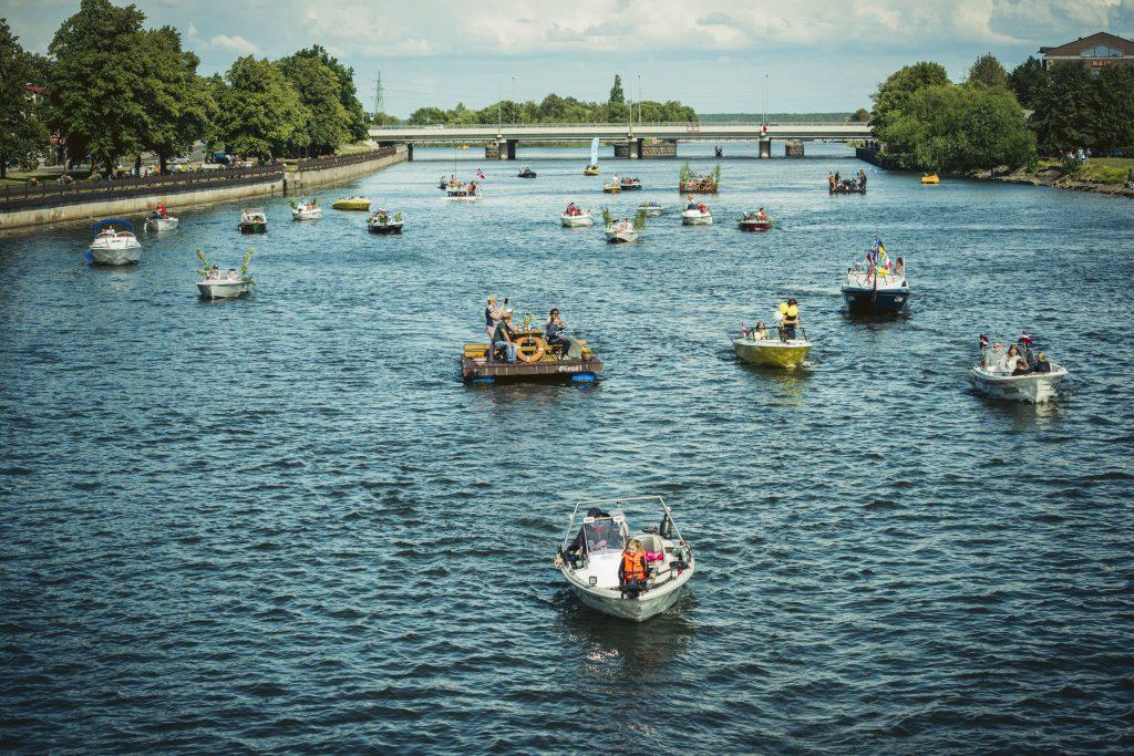 Kanāls ar ūdenī esošiem daudziem laivotājiem