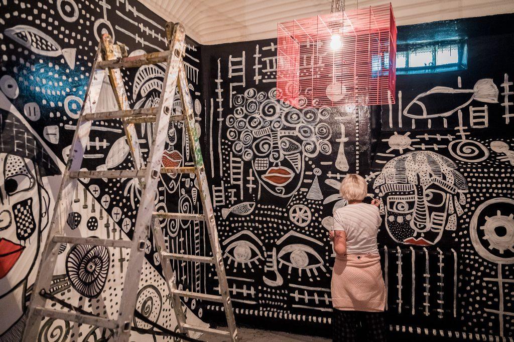 Melna siena, uz kuras sazīmēti daudz smalki, balti zīmējumi, sieviete pie sienas turpina zīmēt