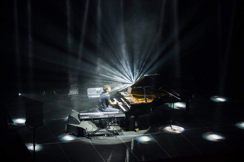 Uz izgaismotas skatuves pianists spēlē klavieres