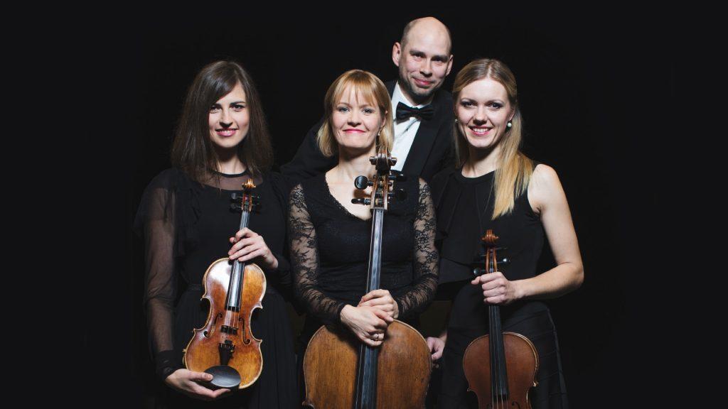 Četri mūziķi, tŗis sievietes priekšplānā un vīrietis aiz viņas, uz tumša fona