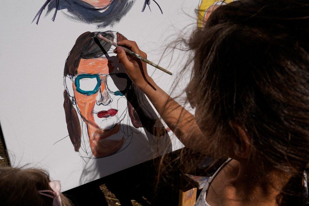 Sieviete uz papīra lapas glezno sievietes tēlu.