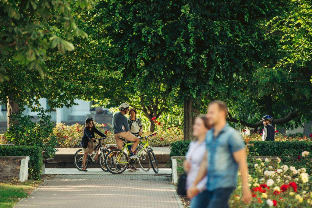 Pilsētas zaļā ainava, koki, cilvēki iet garam, tālumā velobraucēji apstājušies sarunai