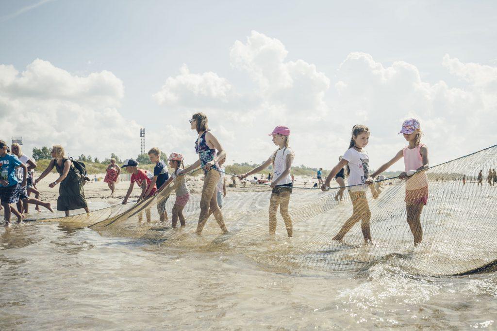Bērni velk tīklu jūrā