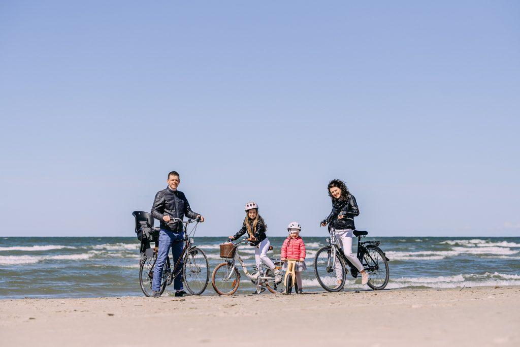 Ģimene ar bērniem uz velosipēdiem pie jūras