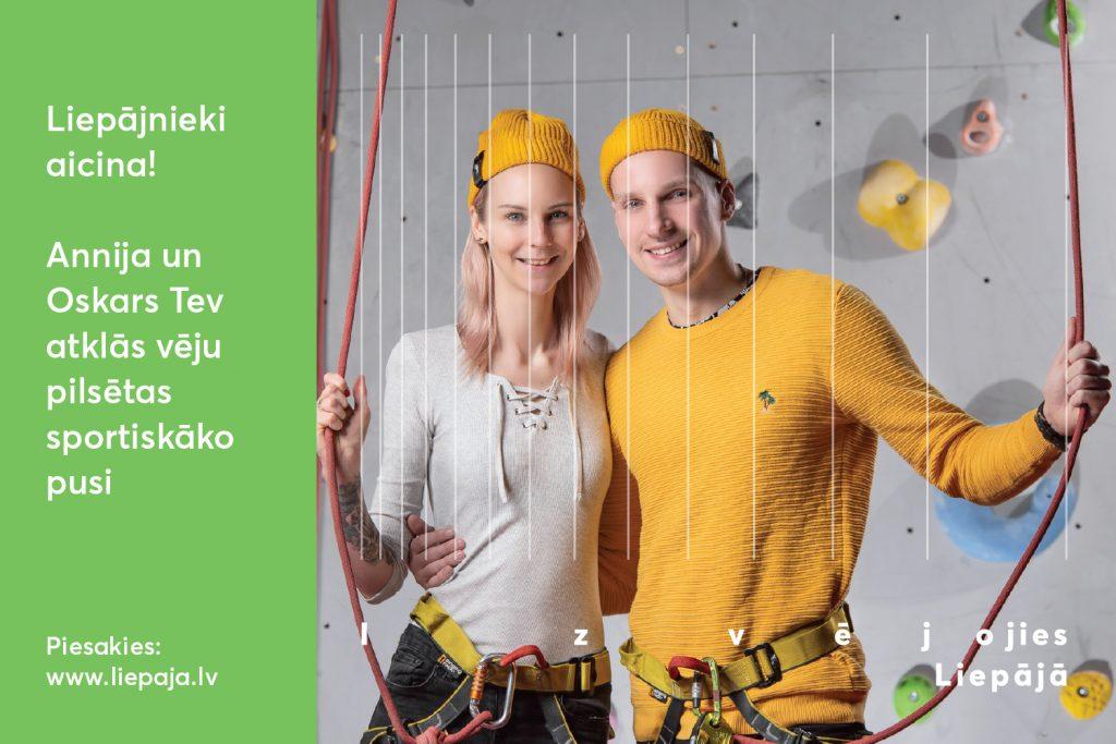 Divi jaunieši dzeltenās cepurēs stāv smaidīgi pie klinšu sienas