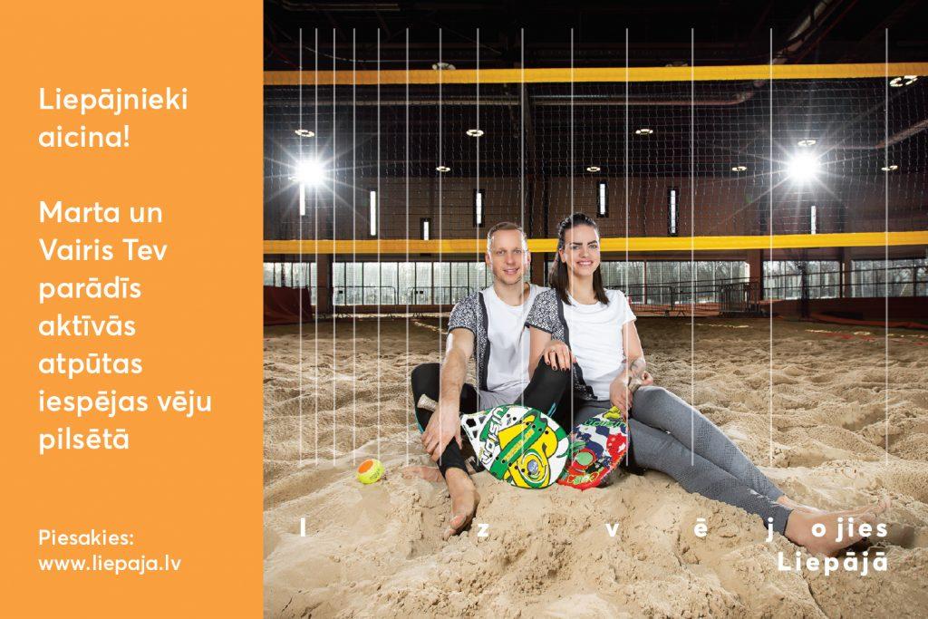 Puisis un meitene sēž pludmales volejbola laukuma smiltīs ar volejbola bumbu rokās