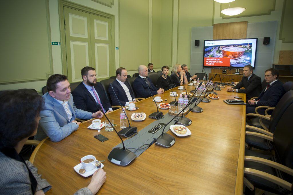 Vairāki cilvēki sēž pie gara galda, galda galā prezentācija uz liela ekrāna