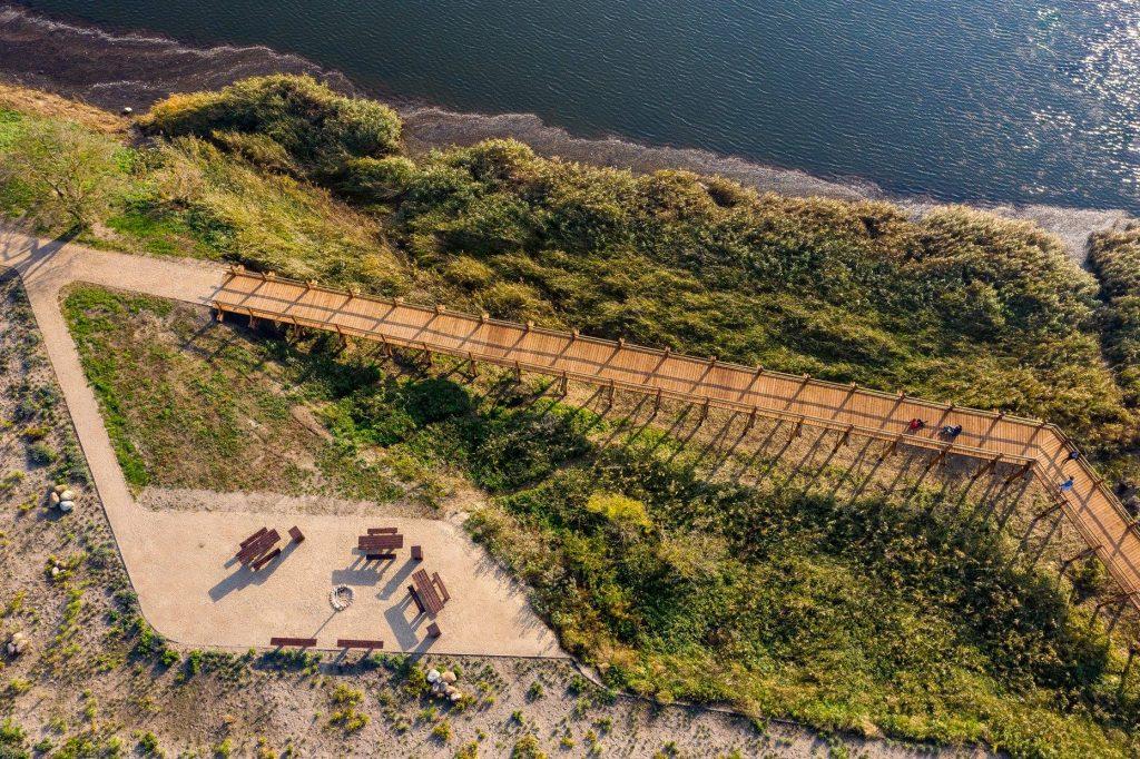 Skats no putnu lidojuma uz zemi, kur ir piknika vieta, koka laipas un ezers.