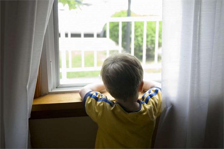 Mazs bērns stāv pie loga un skatās uz pagalmu