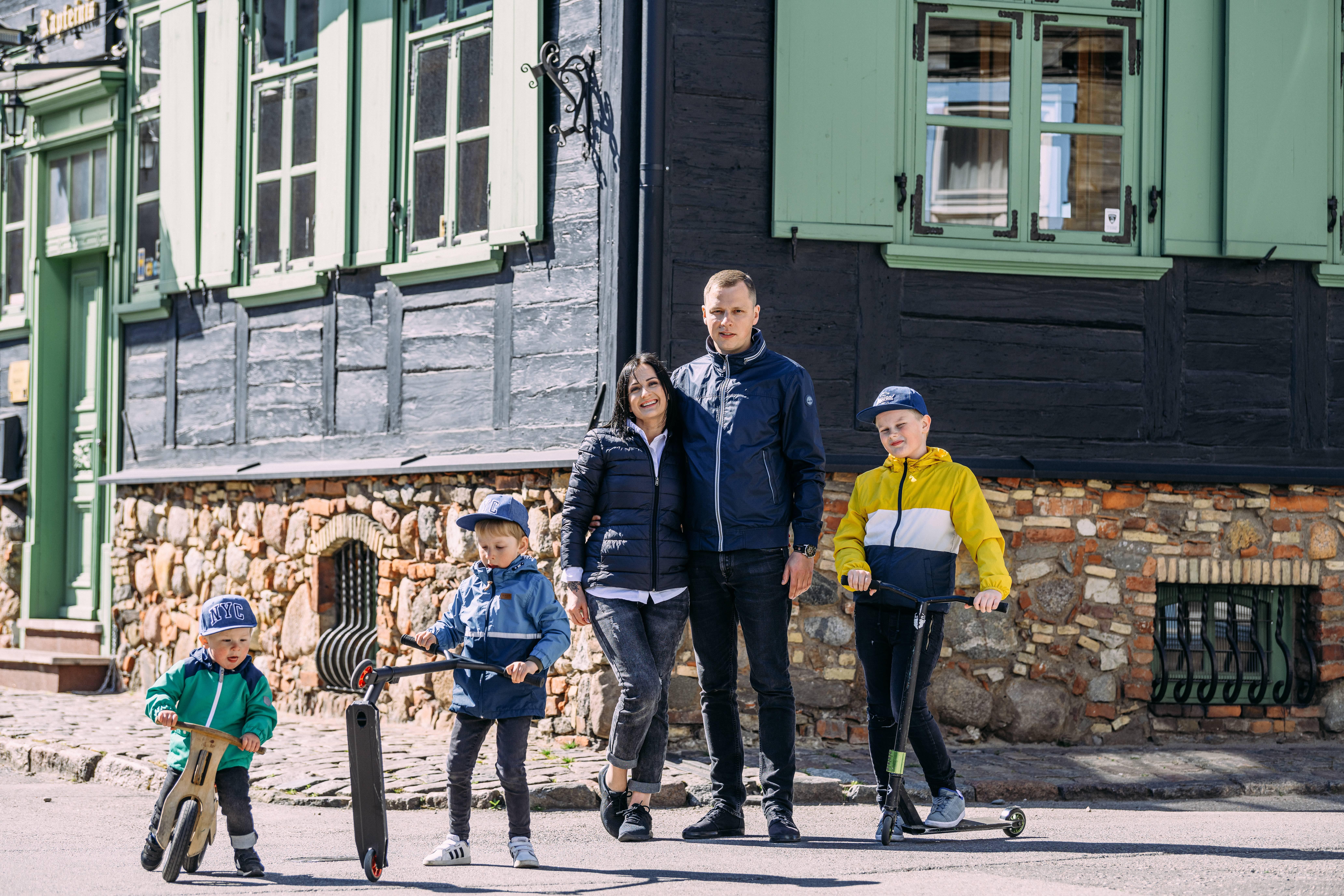 Ģimene ar trīs dēliem uz skrejriteņiem stāv pie senlaicīgas ēkas