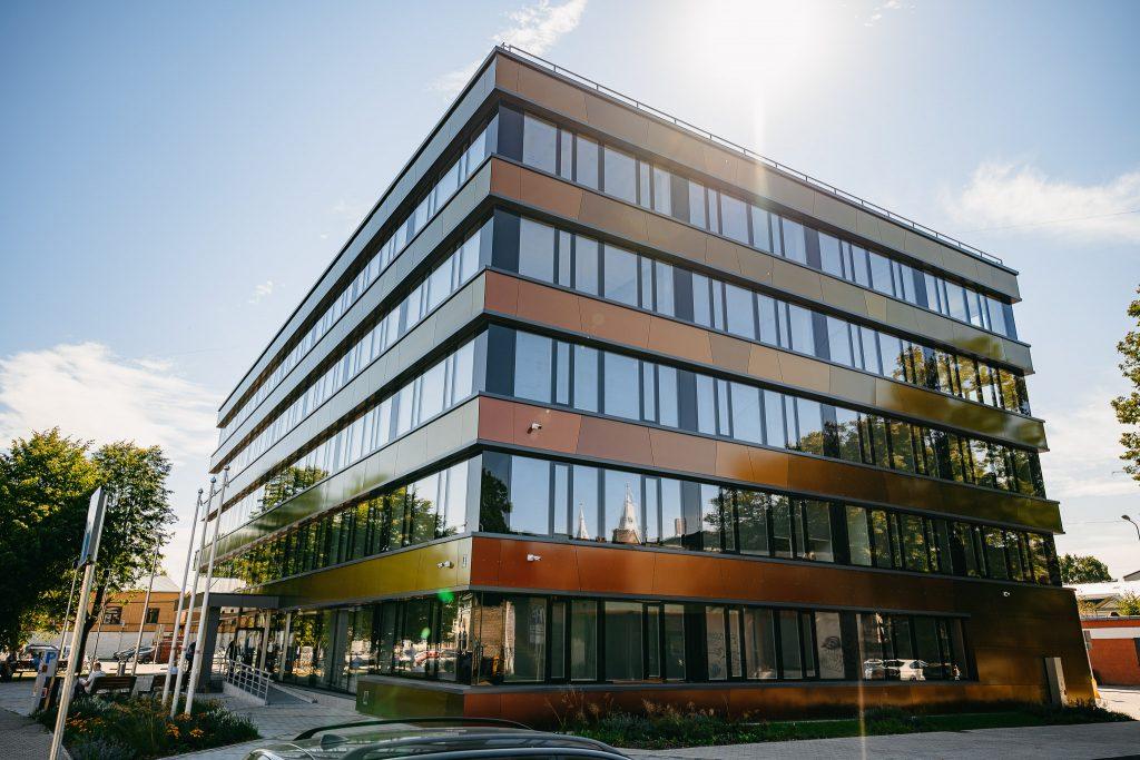 Vairāku stāvu ēka ar stikla logiem un spīdīgu fasādi
