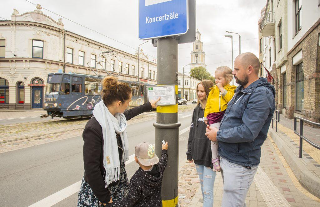 Sabiedriskā transporta pasažieri piestājuši pie pieturas un skata transporta kustības sarakstu