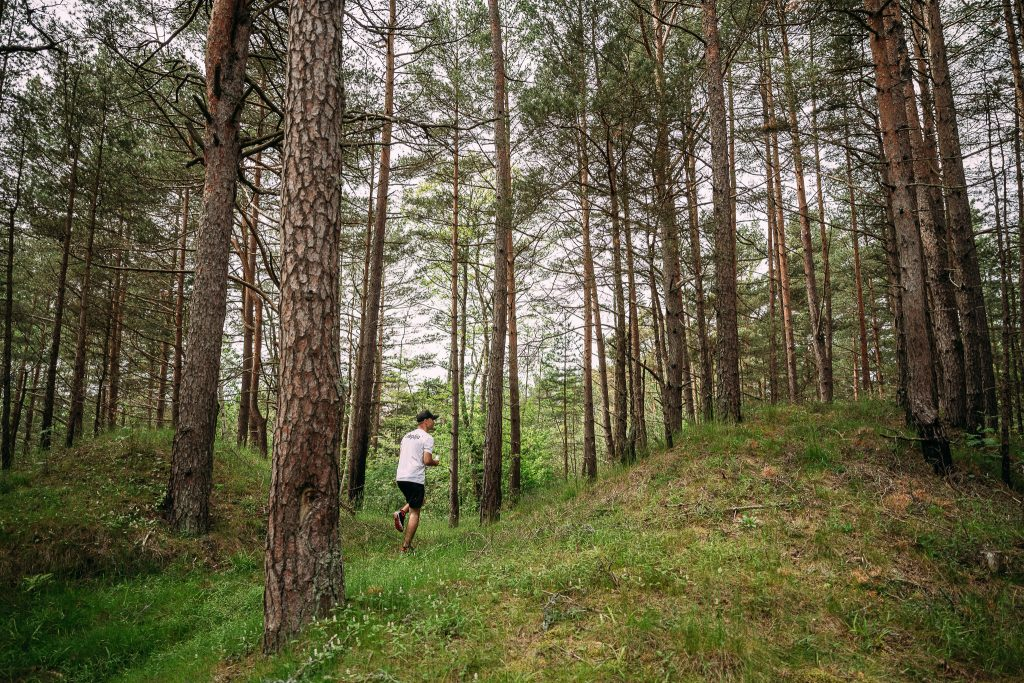 Cilvēks skrien pa mežu