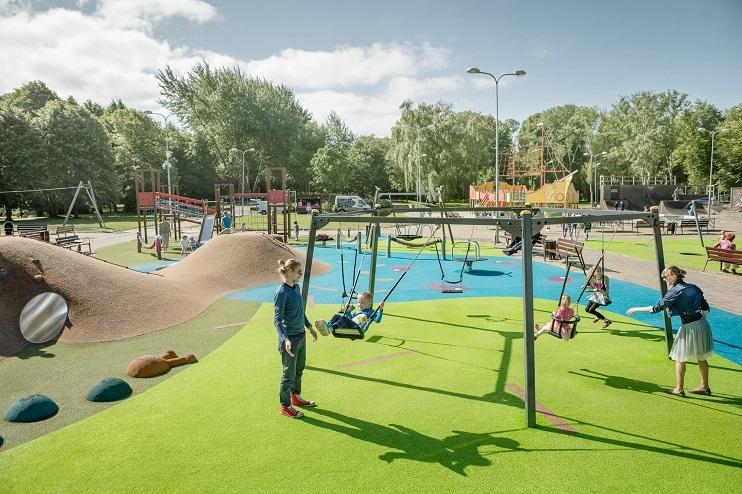 Bērnu rotaļu laukums, kurā vecāki spēlējas ar savu bērnu.