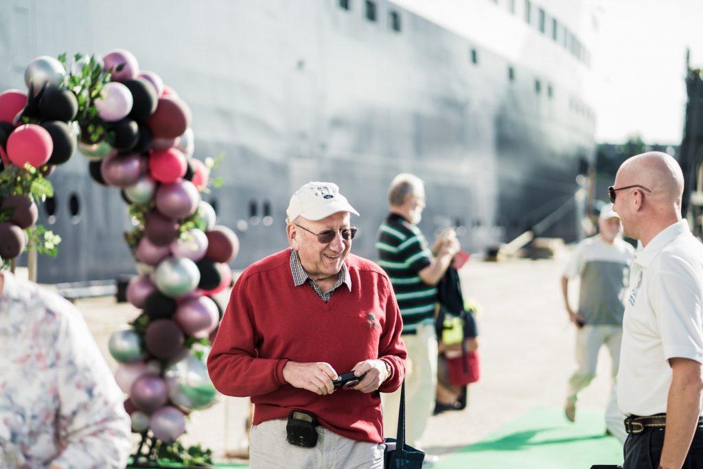Tūrists sarkanā džemperī, fonā kruīza kuģis