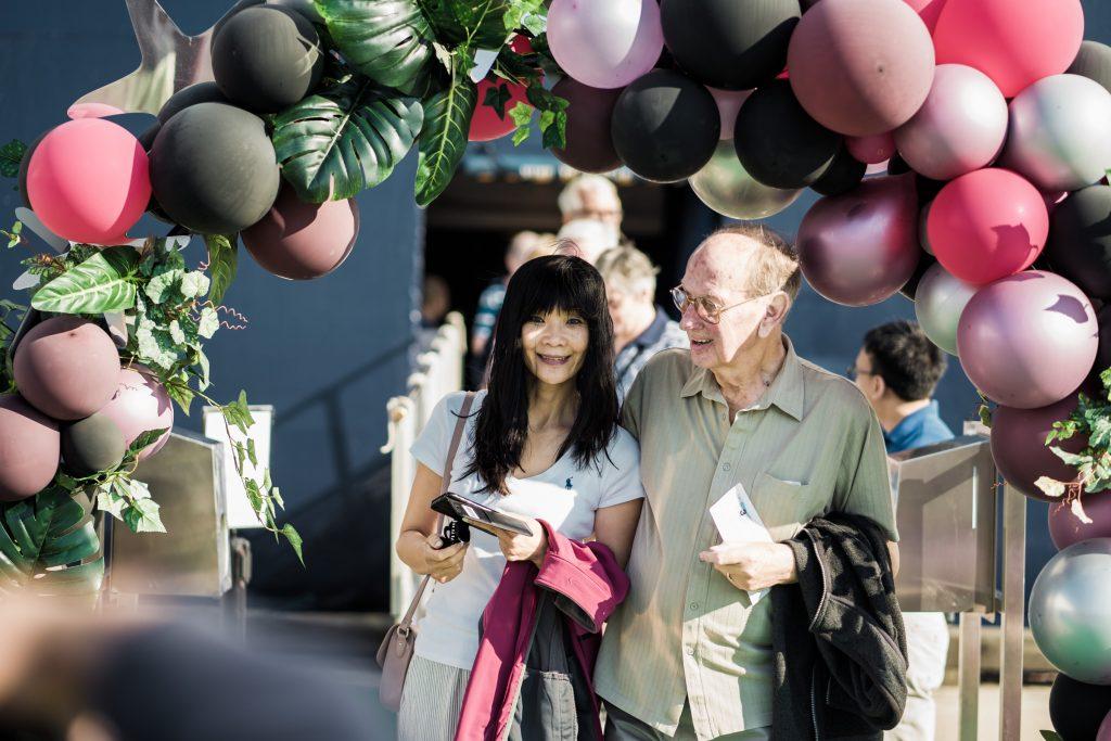 Tūristi ar baloniem izgreznotā arkā