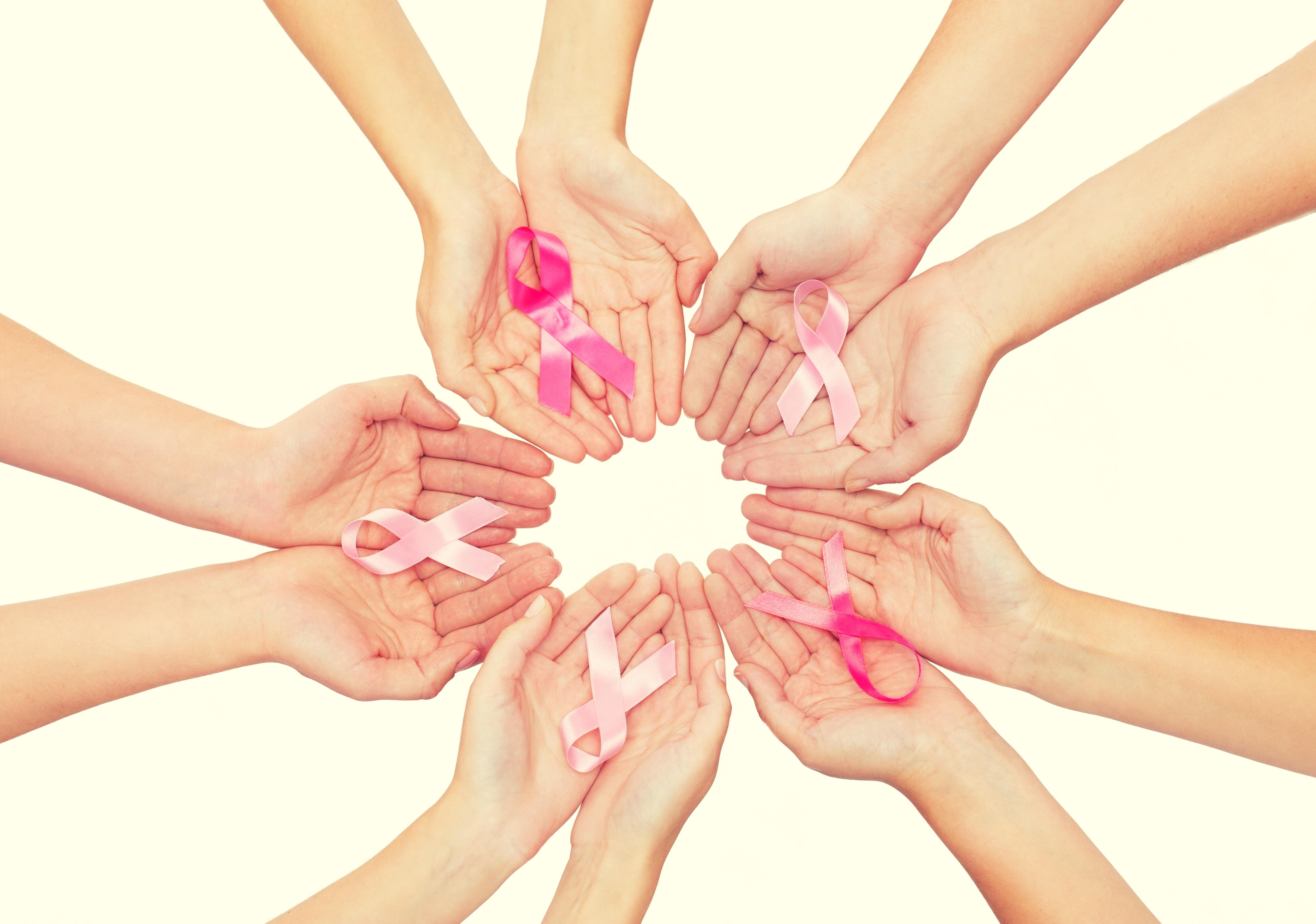 Vairākas sieviešu rokas aplī tur salocītu rozā lentīti