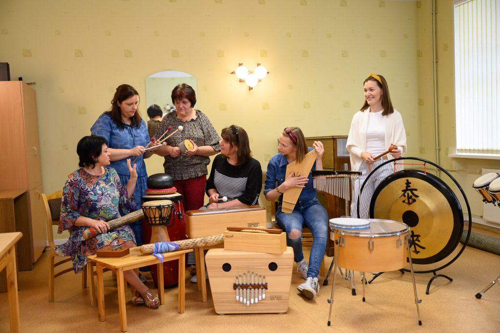 Sievietes stāv un sēž starp mūzikas instrumentiem